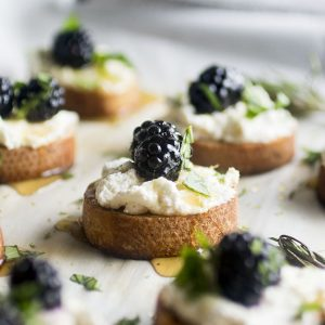 round pieces of toasted baguette on a sheet pan. Each is topped with white cheese, honey, blackberry and chopped basil